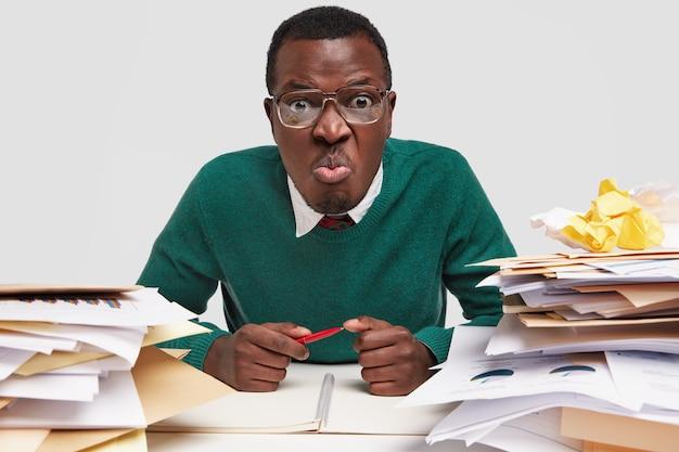 Homem workaholic descontente faz careta, segura a caneta, tem muita papelada, olha fixamente através de grandes óculos com lentes grossas