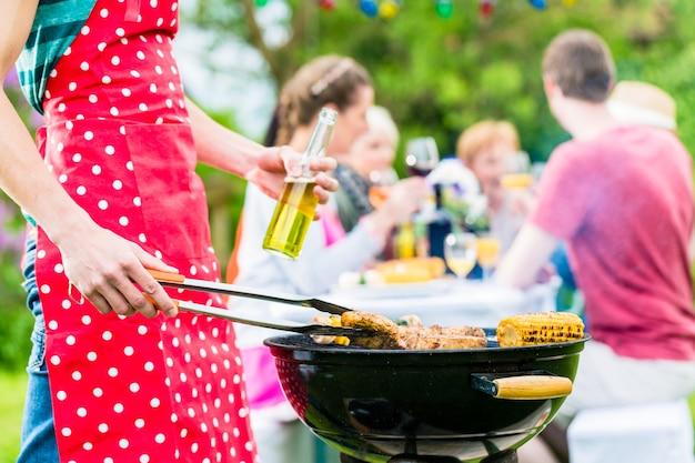 Homem yong na churrasqueira virando a carne, ao fundo, amigos estão dando uma festa no jardim