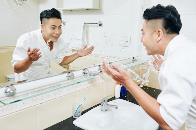 Homem yuong jogando água na pia