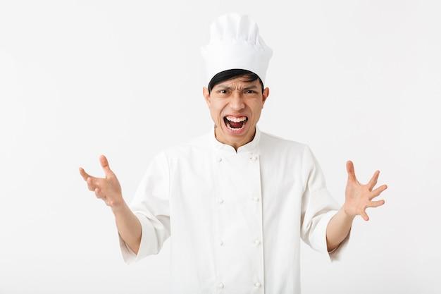 Homem zangado asiático com uniforme de cozinheiro branco e chapéu de chef gritando para a câmera em pé, isolado sobre uma parede branca