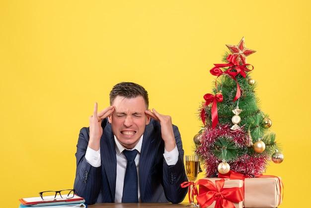 Homem zangado de frente, colocando os dedos na têmpora, sentado à mesa perto da árvore de natal e presentes em fundo amarelo