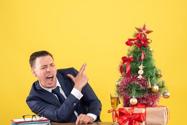 Homem zangado de frente fazendo sinal de arma com o dedo sentado à mesa perto da árvore de natal e presentes em fundo amarelo