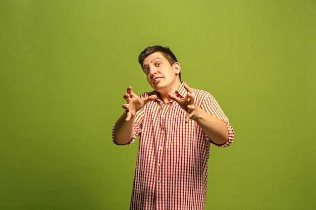 Homem zangado e emocional chorando gritando na parede verde do estúdio