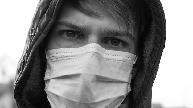 Homem zangado em retrato de máscara médica, depressão em um coronavírus pandêmico ...