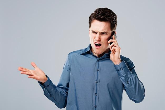 Homem zangado falando ao telefone