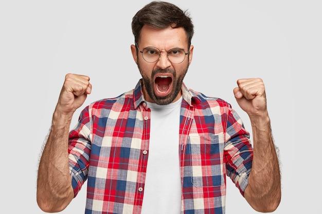 Homem zangado furioso com expressão irritada, aperta os punhos com raiva, grita com alguém, usa camisa xadrez, fica de pé contra a parede branca. emoções e sentimentos humanos negativos. linguagem corporal