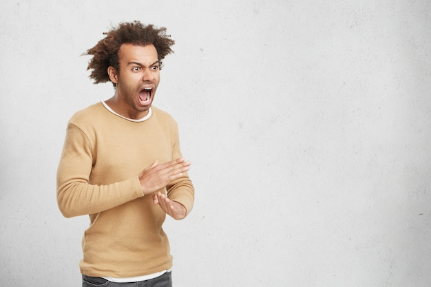 Homem zangado homem mostra gesto de pare, cruza as mãos, pede para não incomodá-lo