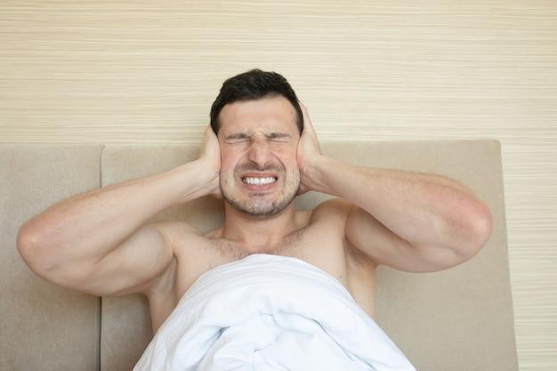 Homem zangado na cama, acordado por um barulho.