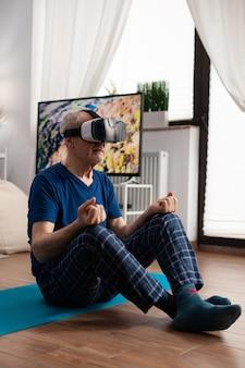Homem zen sênior sentado na esteira de ioga em posição de lótus durante o treino de pilates na sala de estar, alongando os músculos do corpo. aposentado usando fone de ouvido de realidade virtual fazendo meditação