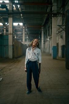 Homem zumbi, humano morto-vivo em uma fábrica abandonada, lugar assustador. terror na cidade, ataque de rastejadores assustadores, apocalipse do fim do mundo, monstros malignos sangrentos