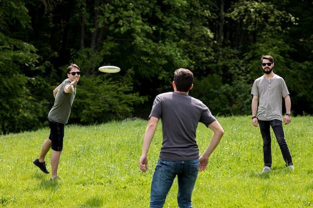 Homens adultos, descansar, parque, jogando frisbee