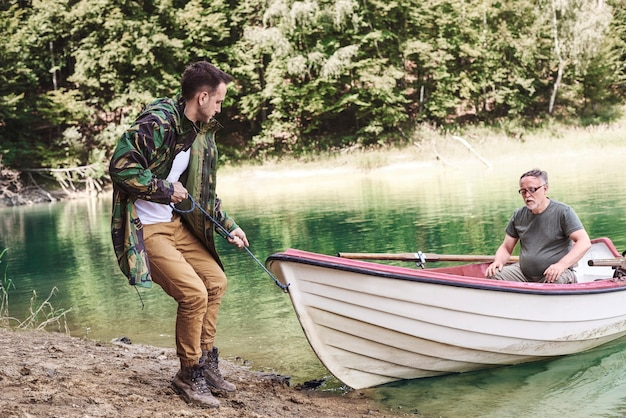 Homens adultos encalhando um barco