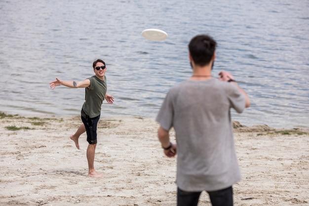 Homens adultos jogando frisbee na praia durante as férias