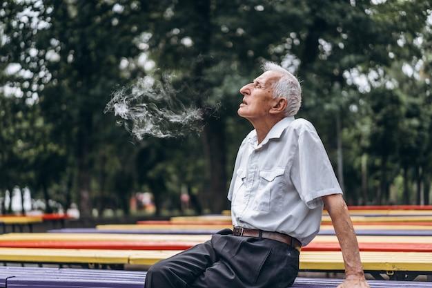 Homens adultos sêniors fumando cigarro ao ar livre no parque da cidade quando estão sentados no banco.