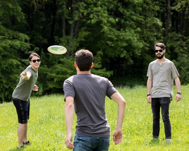 Homens adultos, tendo divertimento, enquanto, jogando frisbee