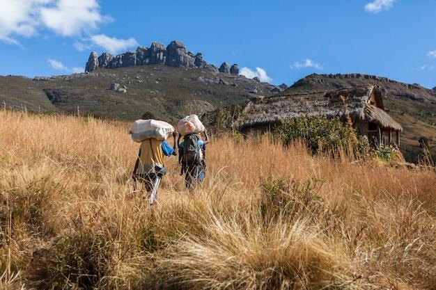 Homens africanos carregam malas pesadas no parque nacional de andringitra