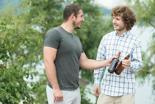 Homens alegres com cerveja passar tempo na natureza