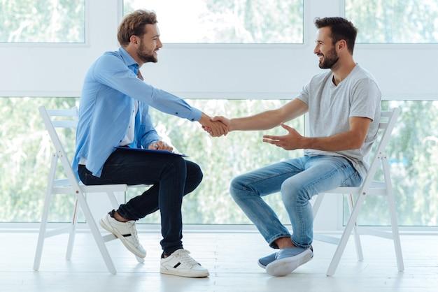 Homens alegres, positivos e encantados, olhando um para o outro e sorrindo enquanto apertam as mãos