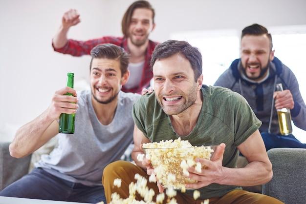 Homens animados assistindo jogo na tv