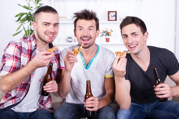 Homens animados estão assistindo futebol com cerveja e pizza.