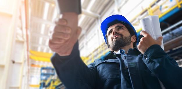 Homens, apertando as mãos em uma instalação industrial