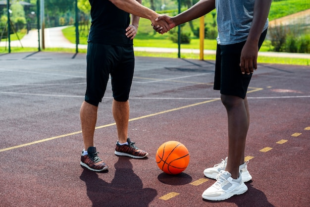 Homens, apertando as mãos na quadra de basquete