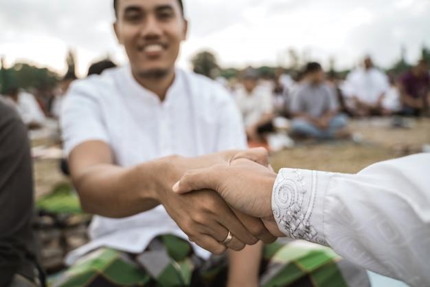 Homens asiáticos apertam as mãos após a oração do eid