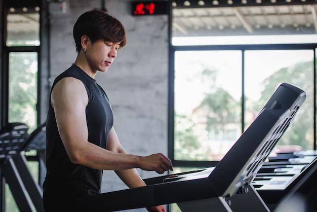 Homens asiáticos bonitos estão exercitando no sportswear e correndo na esteira na academia. esteira elétrica no centro de fitness
