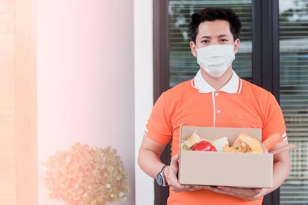 Homens asiáticos carregam mercadorias vestindo uma camiseta laranja manuseie caixas de papel que contêm legumes e frutas