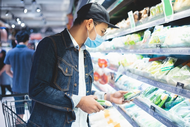 Homens asiáticos compram e compram alimentos para acumular durante o surto de covid
