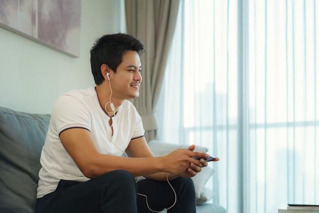 Homens asiáticos descansam ouvindo música com fones de ouvido no sofá da sala de casa.