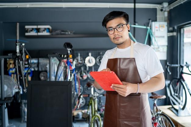 Homens asiáticos dono de loja de bicicleta pequena empresa permanente para receber clientes dentro da loja