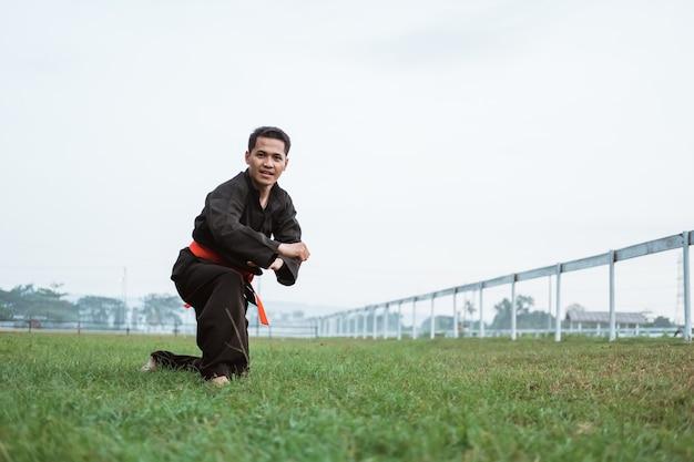 Homens asiáticos em uniformes de silat pencak posam de lado em um parque