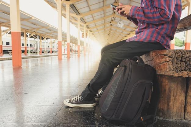 Homens asiáticos estão usando telefones celulares enquanto esperam por trens