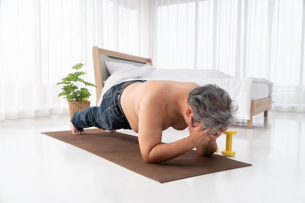 Homens asiáticos gordos estão tentando fazer pranchas com determinação e se esforçando ao máximo para perder peso.