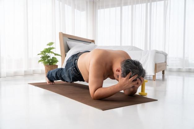 Homens asiáticos gordos estão tentando fazer pranchas com determinação e se esforçando para perder peso ao entrar antes de sair para o trabalho