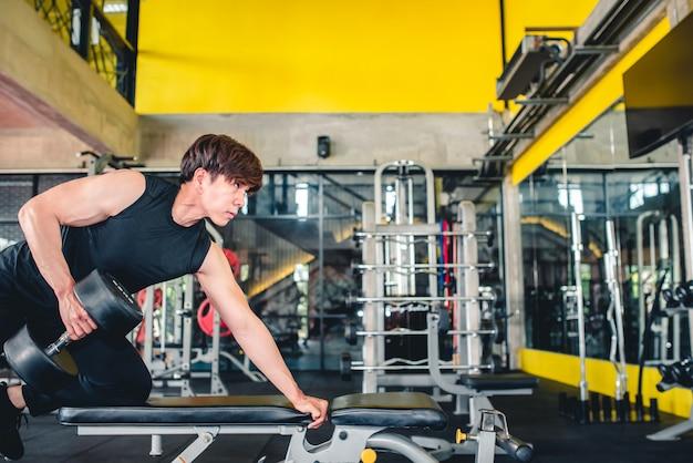 Homens asiáticos que se exercitam com halteres no supino com halteres são uma posição popular para os meninos na academia.