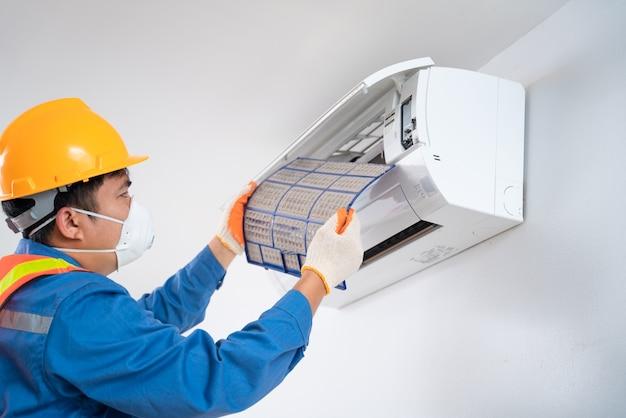 Homens asiáticos usam uma máscara de segurança para evitar que o técnico de poeira retire um filtro de poeira do ar condicionado para limpar o ar condicionado em ambientes fechados.