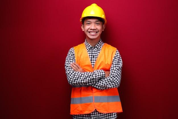 Homens asiáticos usam uniforme de contratado e capacete de segurança com os braços cruzados e olhando para a frente