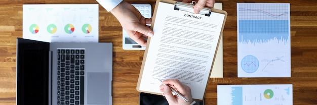Homens assinam contrato em dispositivos de documentos em segundo plano. fonte de informações para pessoas que implementam diretamente o projeto. otimização de marketing com relatórios de gráfico e gráfico. demanda e contrato de mercado