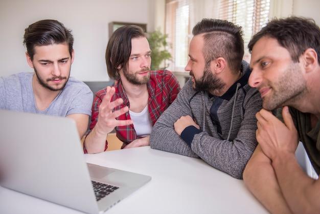 Homens assistindo a um vídeo em um laptop