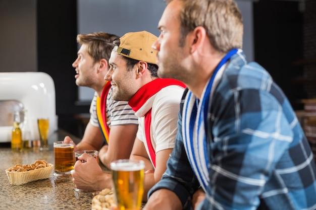Homens assistindo um jogo na tv
