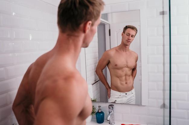Homens atléticos bonitos sem camisa na frente refletem no espelho