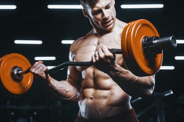 Homens atléticos fortes bonitos, bombeando os músculos treino barra conceito de musculação