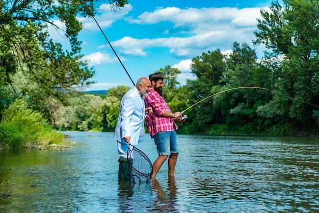 Homens barbudos pescadores um pouco mais velhos divertem e relaxam a diferença entre a pesca com mosca e a pesca normal ...
