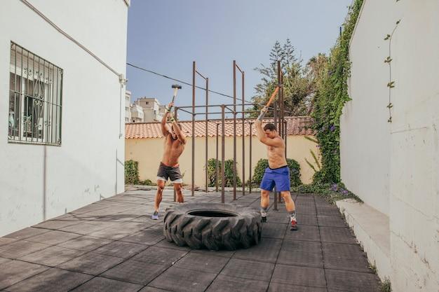 Homens batendo com martelos na roda
