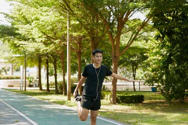 Homens bonitos asiáticos se aquecem antes de caminhar e correr no parque pela manhã.