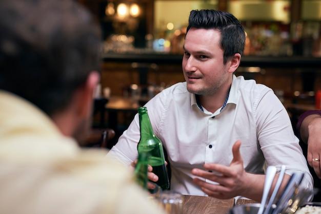 Homens bonitos bebendo cerveja no bar