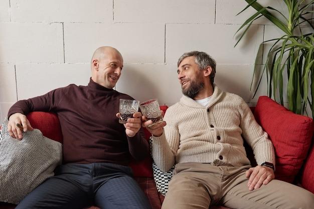 Homens bonitos de meia-idade positivos sentados em casa e copos de uísque tilintando