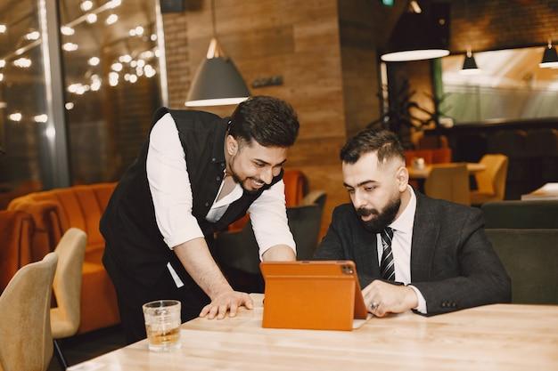 Homens bonitos de terno preto, trabalhando em um café